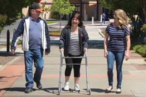 Karen Parrish, center, walks with her husband, Jerry, and daughter, Heather Parrish-Salinas following hip replacement surgery.